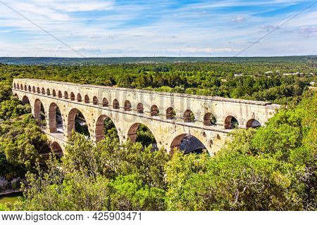 The Pont du Gard is the tallest Roman aqueduct. The aqueduct Pont du Gard connects hills covered with dense deciduous forest. The Gardon River in a bright sunny day. Interesting trip to France.