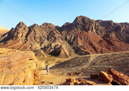 Woman in a blue jacket enthusiastically photographs strange rocks of red-orange sandstone. Multicolored landscape formations. The Eilat Mountains. Israel.