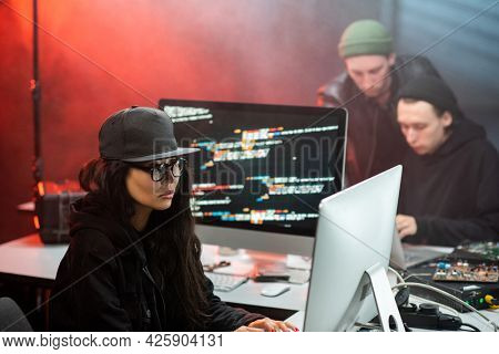 Young Asian woman in hacker attire and two guys decoding information