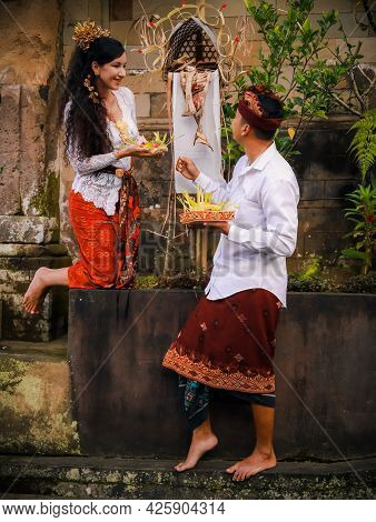 Traditional Balinese Ceremony. Multicultural Couple Making Hindu Religious Ceremony With Offerings.