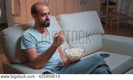 Caucasian Male Chilling On Sofa With Popcorn Bowl In Hands While Watching Movie Series On Television