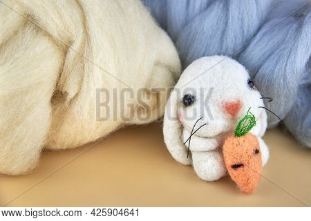 Felted Handmade Bunny With Carrot Near The Skeins Of Wool.
