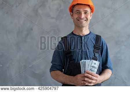 A Happy Worker In A Protective Helmet Received A Salary Of American Dollars And Holds Them In His Ha