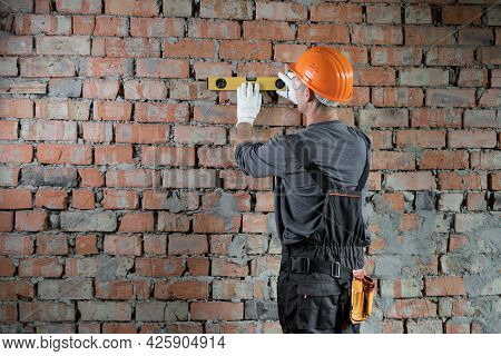 Back View Of A Builder In Overalls And A Helmet Measures The Wall With A Construction Tape. A Male F