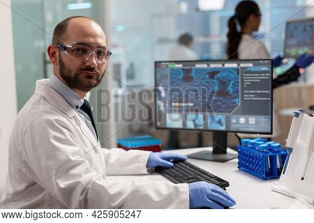 Portrait Of Scientist Man Looking At Camera Sitting In Modern Equipped Laboratory. Scientist Doctor