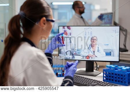 Scientist In Medicine Laboratory Discussing With Professor During Video Online Conference Showing Bl