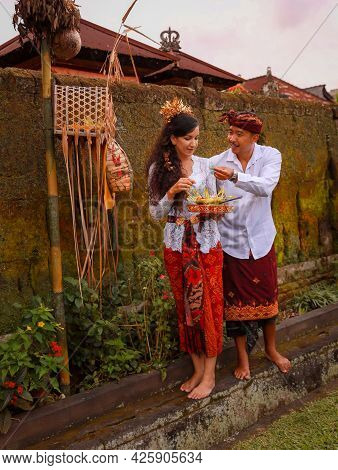 Traditional Balinese Ceremony. Multicultural Couple Making Hindu Religious Ceremony With God's Offer