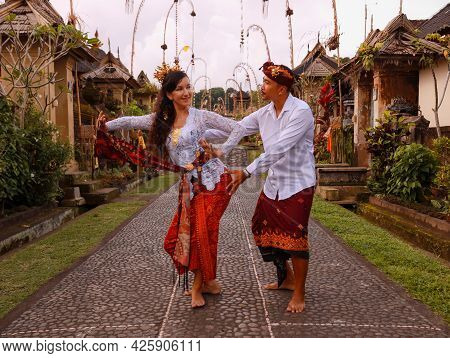 Multicultural Couple Dancing Traditional Balinese Dance. Penjor Bamboo Decoration. Caucasian Wife An