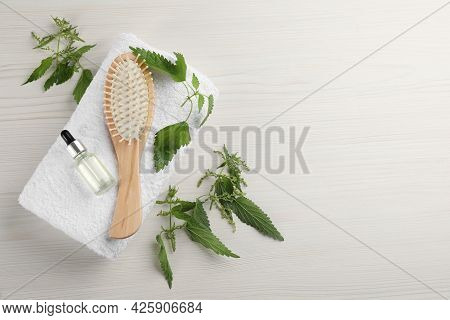 Stinging Nettle, Extract, Towel And Brush On White Wooden Background, Flat Lay With Space For Text.