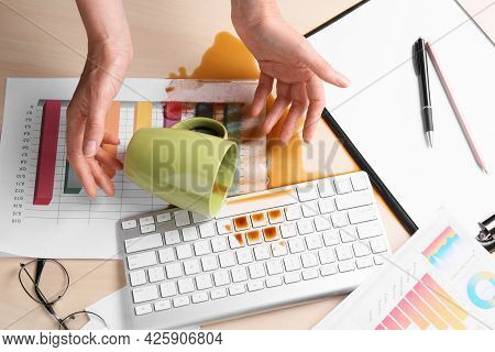 Woman With Coffee Spilled Over Her Workplace, Above View