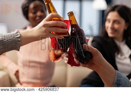 Close Up Of Bottles And Cups Of Beer From Cheerful Friends After Work At Office Party. Multi Ethnic
