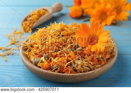 Plate Of Dry Calendula Flowers On Light Blue Wooden Table, Closeup