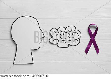 Human Head And Brain Cutouts Near Purple Ribbon On White Wooden Background, Flat Lay. Epilepsy Aware