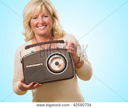 Mature Woman Holding Vintage Radio against a blue background