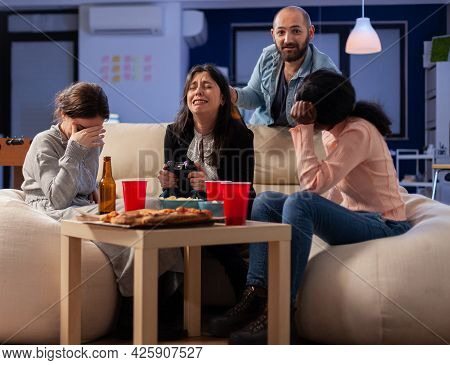 Diverse Group Of Mates Bonding While Playing Video Game On Tv Console Losing With Joystick Controlle