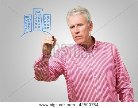 Mature Man Drawing Buildings On Glass, Indoors