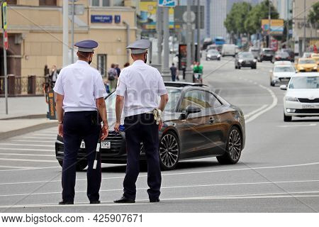Moscow, Russia - July 2021: Two Traffic Police Officers In Masks Standing On The Road. Policemen On