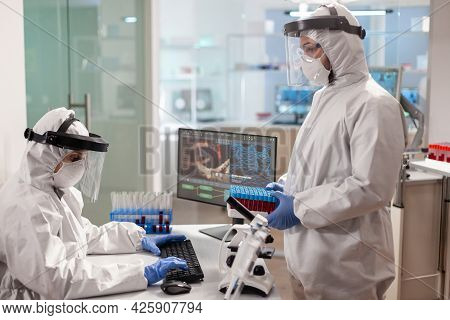 Scientists In Protection Suits Analysing Test Tubes With Blood Sample In Chemical Lab. Team Doctors