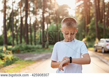 Little Blonde Boy Using Fitness Bend Touching Button And Touchscreen While Posing Outdoor In Park, T