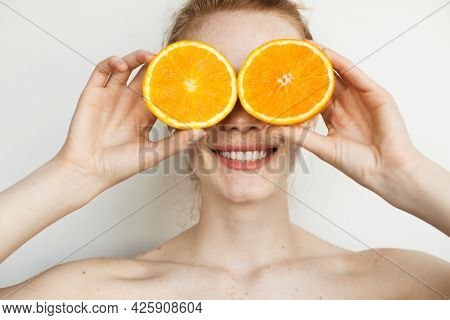Smiling Ginger Woman With Freckles Is Covering Her Face With Sliced Oranges Posing On A White Wall