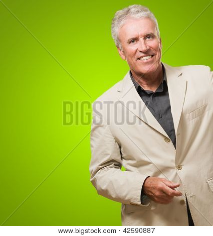 Senior Man Wearing A Suit against a green background