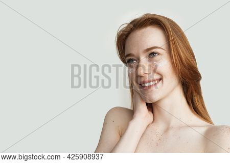 Woman With Freckles And Red Hair Is Posing On A White Studio Wall Applying On A Her Face Anti Aging
