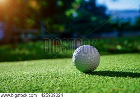 Close-up View Of Golf Ball On The Green Grass. Golf Ball On Fairway Of Beautiful Golf Course At Summ