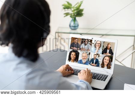 Male Employee Involved Video Meeting On The Laptop With Diverse Workteam, Indian Man Using Computer