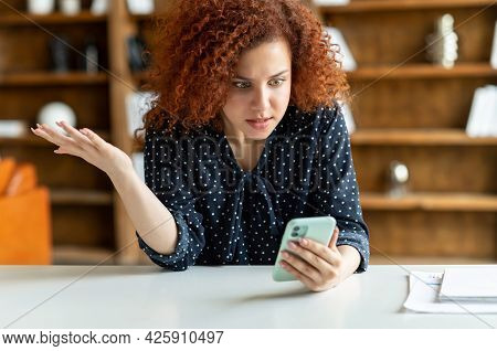 Shocked Red-haired Curly Woman Holding A Smartphone, Feel Astonishment With A Bad News, Fired From W