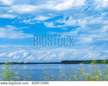 The Summer Scene In Motion Of The Field Grass In Front Of The Lake And The Sky. Poor Focus For The A