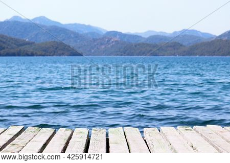 Beach Vacation On The Sea, Background For Summer Vacation And Travel. View From Old Wooden Pier To D