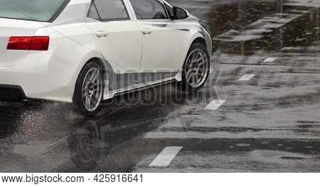 Heavy Rain And Puddles On The Road Cause Skidding Or Sliding Of A Cars Tires Across A Wet Surface
