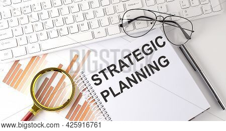 Strategic Planning Text Written On Notebook With Keyboard, Chart,and Glasses