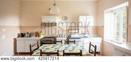 Interior of an old kitchen, almost antique, a table in the middle, the space is large and it is also bright. There is no style.