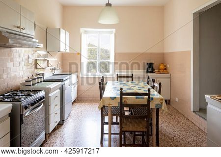 Interior of an old kitchen, almost antique, a table in the middle, the space is large and it is also bright.