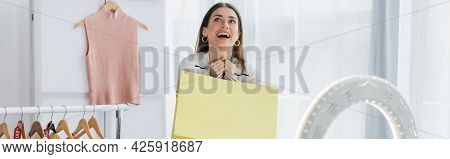 Astonished Fashion Blogger Holding Shopping Bag Near Clothes And Ring Lamp, Banner.