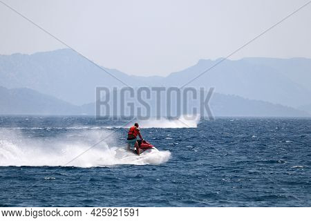 Man Rides A Water Scooter On The Aegean Sea On Misty Mountains Background. Water Sport, Riding A Jet