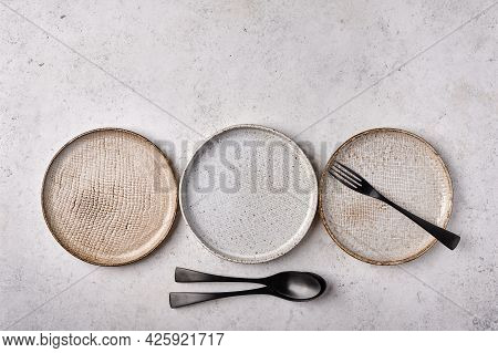 Empty Light Plates With Fork And Spoon Set On Gray Wooden Background. Top View, Copy Space
