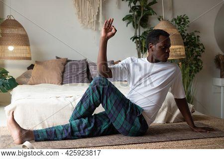 Man Doing Yoga Spine Twisting Pose Or Ardha Matsiendranasana Sitting At The Living Room