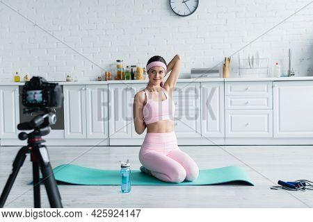 Sportive Woman Stretching On Fitness Mat Near Blurred Digital Camera In Kitchen.