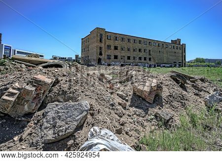 Abandoned Multi-story Red Brick Factory Building With Broken Glass Windows Standing Alone In A Field
