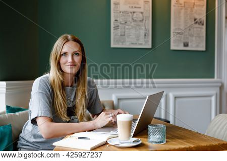 Portrait Of Young Woman Using Technology Of Smartphone And Looking At Laptop. Young Woman Freelancer