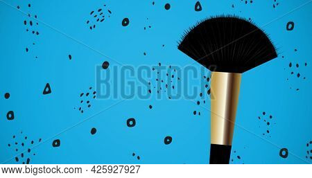 Composition of make up brush with shapes repeated on blue background. fashion and accessories background pattern concept digital image.