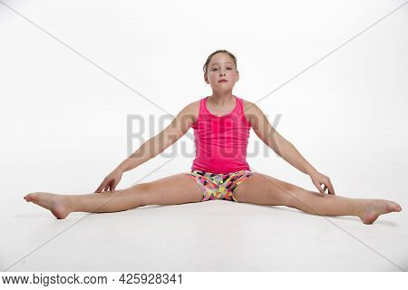 A Young Tween Girl Streching For A Dance Routine.