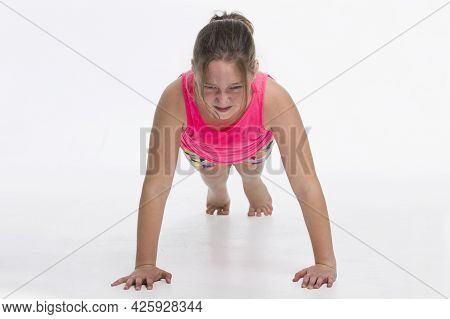 A young tween girl doing push ups with a determined expression.