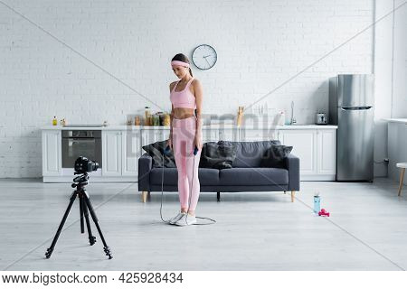 Sportive Woman With Jump Rope Recording Lesson On Digital Camera At Home.