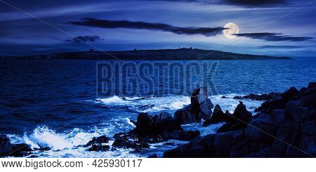 Seascape At Night. Wonderful Scenery With Island And Cliffs On The Shore In Full Moon Light. Clouds