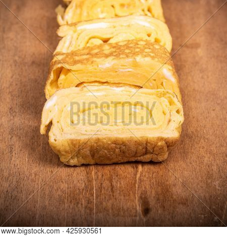 Japanese Omelet Tamago Yaki Cut Into Pieces On A Wooden Background, Close-up