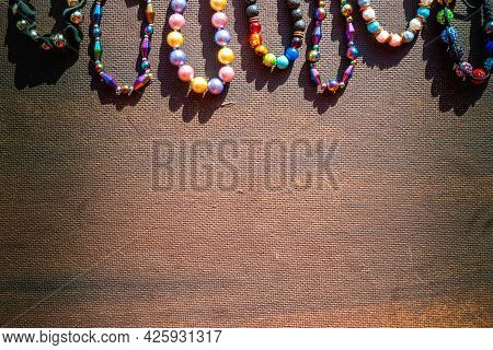 Heap Of Colored Bright Jewelry Beads On A Dark Background. Different Gems Beads Necklace. Jewel Neck