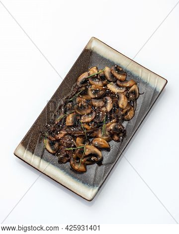 Fried Mushroom Slices And Thyme On Platter. Rectangular Clay Plate With Cooked Champignons Isolated